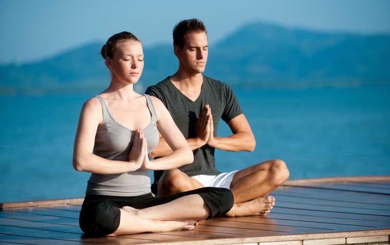 couple-meditating-on-pier-o