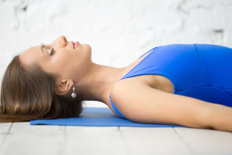 woman-lying-on-back-practicing-breathing-o
