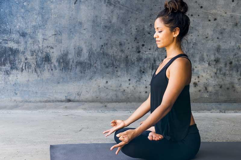 woman-meditating-against-urban-background-o