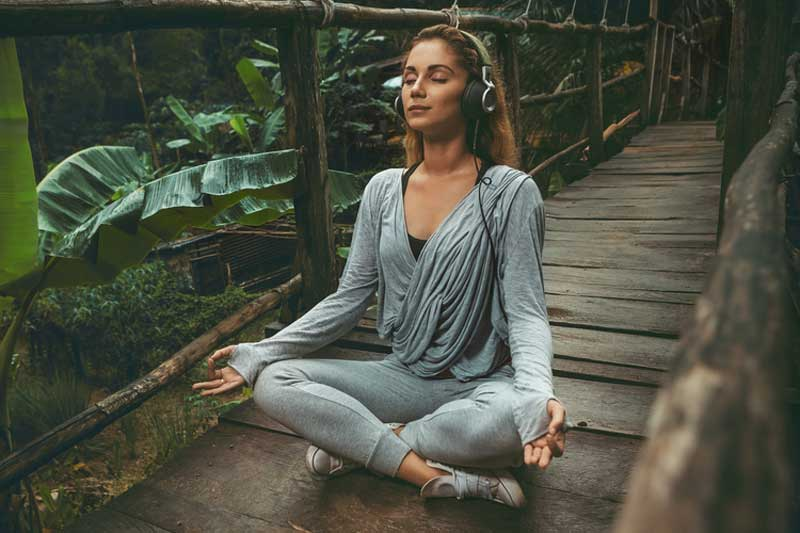 woman-meditating-to-music-in-the-rainforest-o